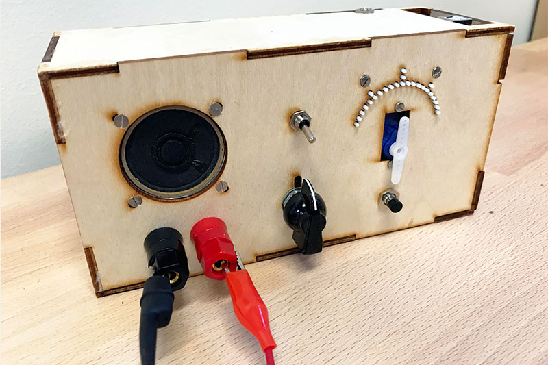 A wooden box which houses the hardware for the accessible voltmeter. The front has buttons, tactile marks, lead probes, and  a speaker panel.