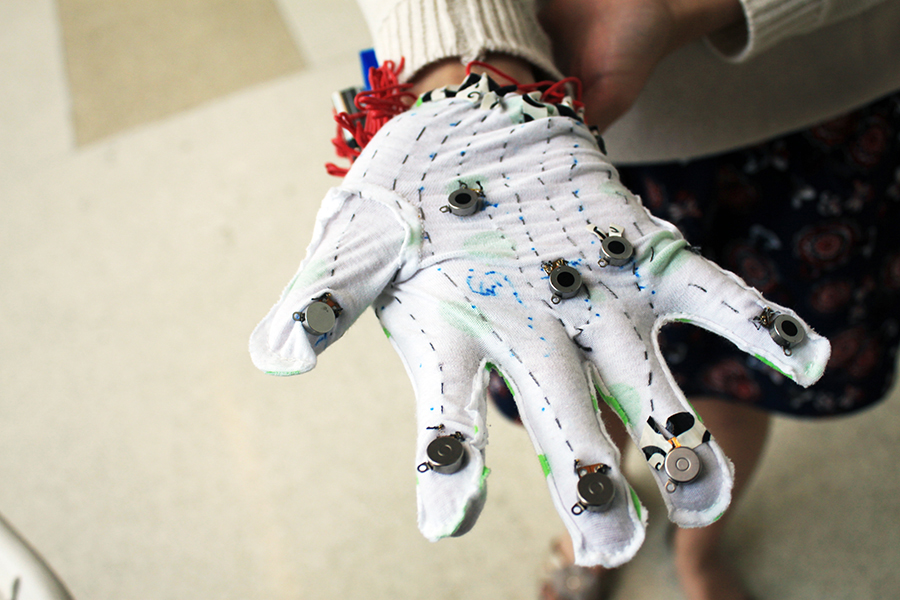 TouchMusic glove. White color with coin cell vibration motor and LEDs sewed on it.